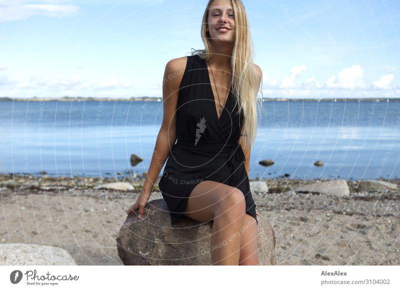 Lächelnde, junge Frau in schwarzem Kleid an der Ostsee Stil Freude schön Wohlgefühl Sommer Sommerurlaub Sonne Sonnenbad Strand Meer Junge Frau Jugendliche