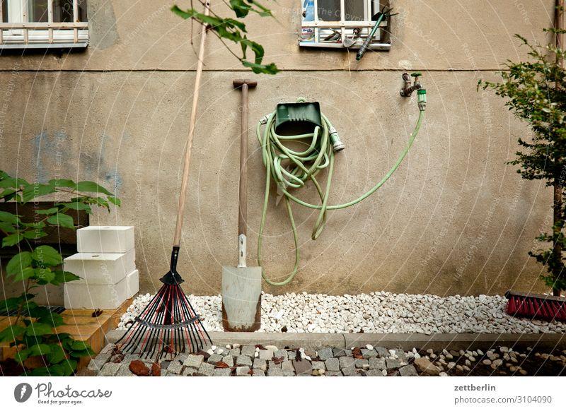 Garten im Hinterhof Gartengeräte Schlauch Gartenschlauch Wasser Wasserhahn Wasserschlauch Spaten Schaufel Häusliches Leben Wohnhaus Fassade Fenster Gitter Kies