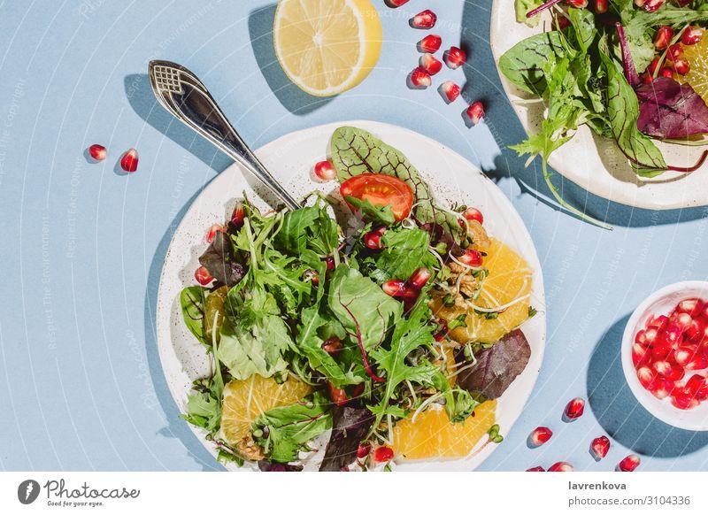 Flachlegung von zwei Zitrussalatplatten Vorspeise Amuse-Gueule Rucola Kirschtomaten Zitrone Zitrusfrüchte Essen zubereiten lecker Diät Abendessen flach