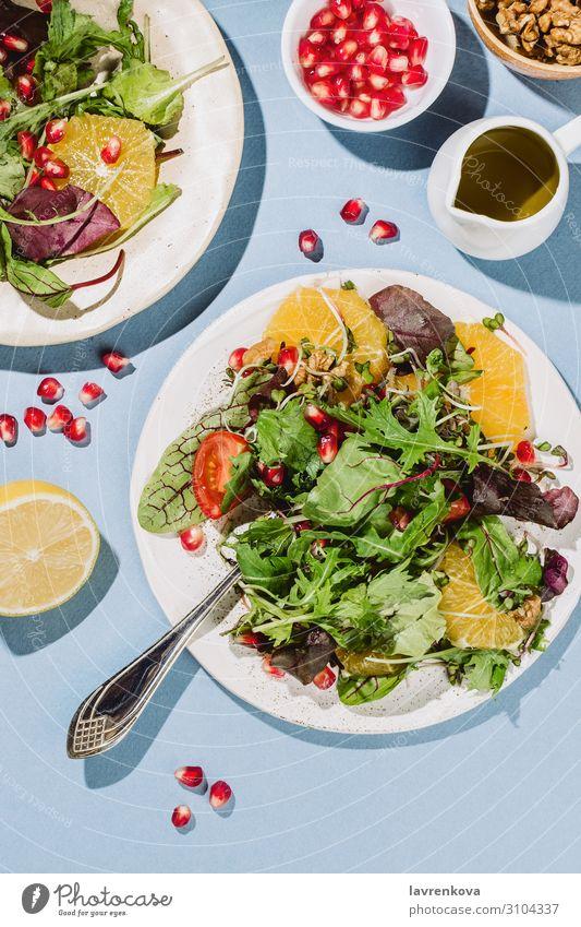 Flachlegung von zwei Zitrussalatplatten Amuse-Gueule Rucola Kirschtomaten Zitrone Zitrusfrüchte Essen zubereiten lecker Diät Abendessen flach Lebensmittel