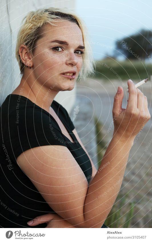 Junge Frau sitzt auf einem Block und raucht eine Zigarette Stil schön Jugendliche 18-30 Jahre Erwachsene Sommer Schönes Wetter T-Shirt Piercing blond kurzhaarig