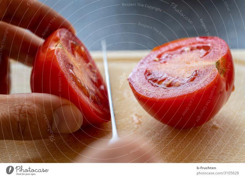 Tomate schneiden Lebensmittel Gemüse Salat Salatbeilage Ernährung Bioprodukte Vegetarische Ernährung Messer Tisch Küche Arbeitsplatz Finger festhalten frisch