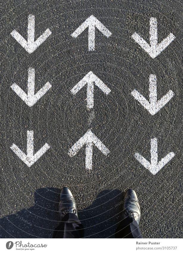 Ein Mann blickt nach unten auf drei Reihen von Pfeilen, von denen eine Reihe nach vorne und die anderen beiden gegen ihn zeigen. Arbeit & Erwerbstätigkeit