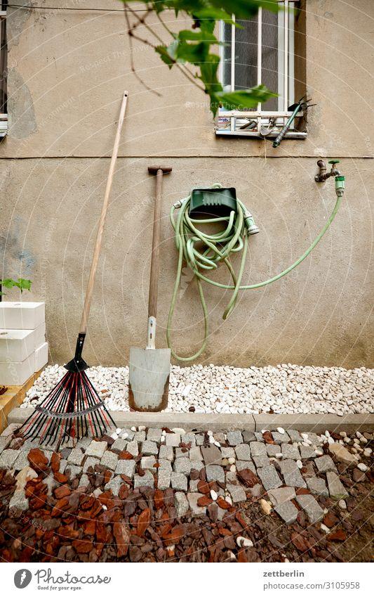 Gartenschlauch Gartengeräte Schlauch Wasser Wasserhahn Wasserschlauch Spaten Schaufel Häusliches Leben Wohnhaus Fassade Fenster Gitter Kies Menschenleer