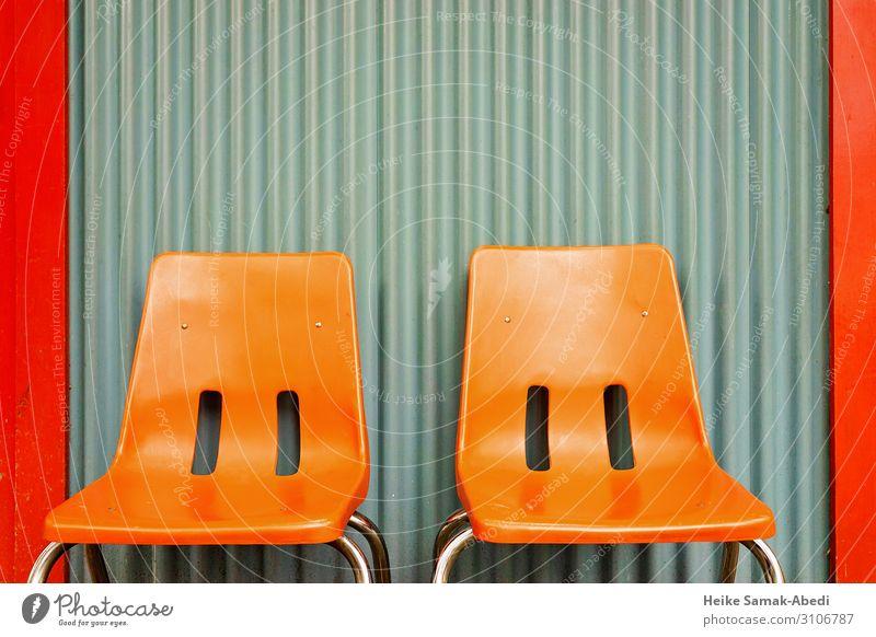 Orangefarbene Stühle vor einer Wellblechwand Innenarchitektur Möbel Stuhl Mauer Wand Fassade sitzen orange Pause ruhig Erholung Farbfoto