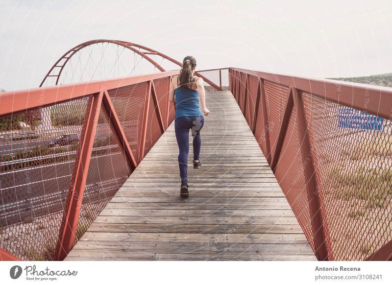 mittlere erwachsene Frau, die auf einer Brücke läuft. Lifestyle Sport Erwachsene Architektur Fußgänger Autobahn Einsamkeit rennen 30s mittlere erwachsene Person