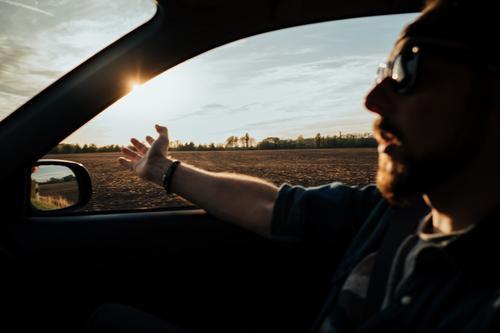 Mann im fahrenden Auto mit Armen aus dem Fenster Abenteuer PKW Kaukasier Landschaft Tag Laufwerk Feld Hände Reise Lifestyle männlich Männer Passagier Person