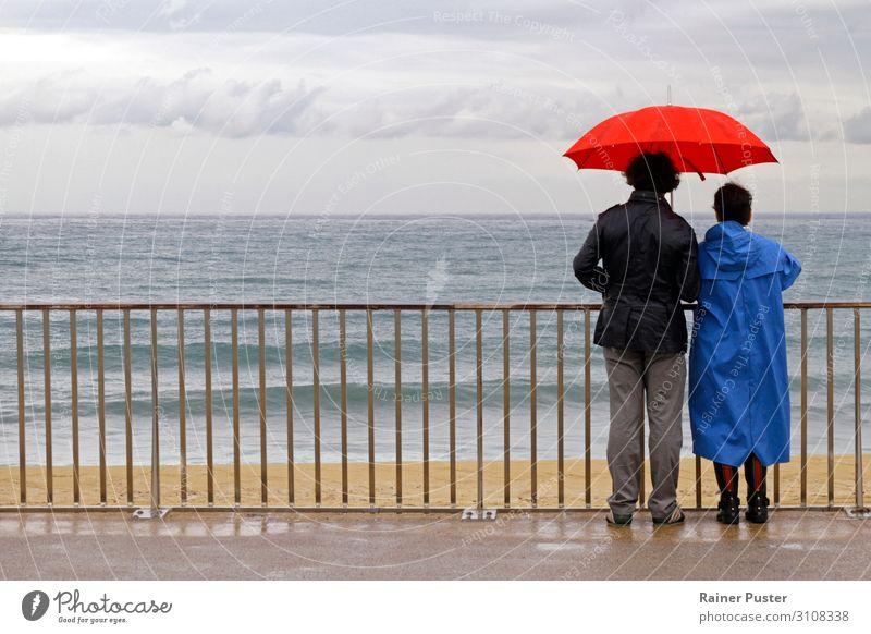 Paar mit Schirm an der Küste bei Barcelona Mensch 45-60 Jahre Erwachsene Wolken Herbst schlechtes Wetter Regen Strand Blick warten Zusammensein Gefühle