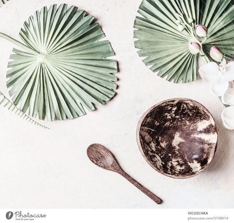 Leere Kokosnussschale mit Löffel auf weißem Schreibtischhintergrund mit tropischen Blättern, Ansicht von oben. Kopierraum für Ihr Design oder Produkt leer