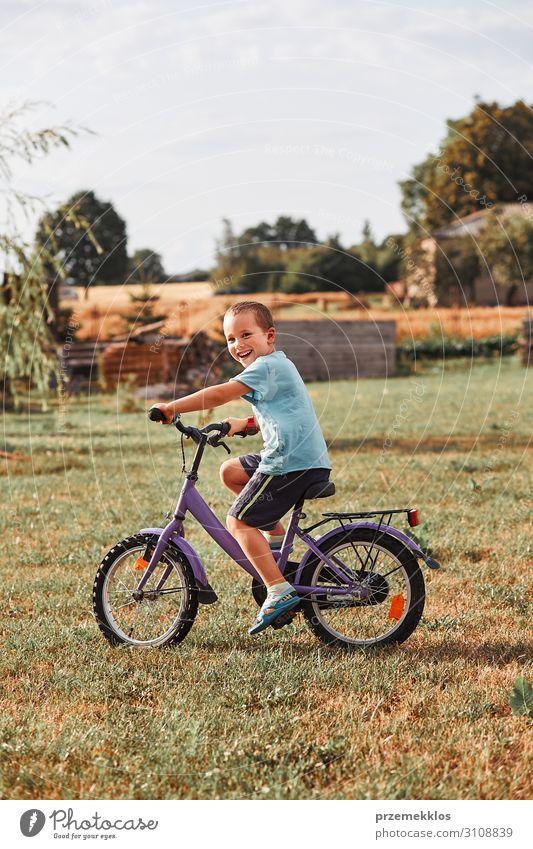 Glücklicher lächelnder Junge auf dem Fahrrad Lifestyle Freude Erholung Freizeit & Hobby Spielen Sommer Garten Kind Schule Mensch Kindheit 1 30-45 Jahre