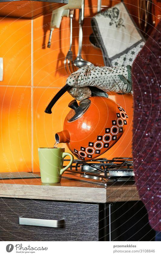 Frau, die Wasser in die Tasse gießt. Frühstück Kaffee Tee Topf Küche Erwachsene 1 Mensch 30-45 Jahre Handschuhe machen authentisch heiß modern Gießen