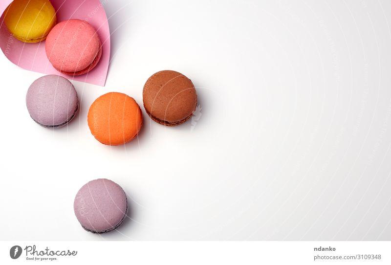 gebackene Makronen in einer rosa Papiertüte Kuchen Dessert Süßwaren frisch lecker oben braun gelb weiß Farbe Tradition Mandel sortiert Sortiment Hintergrund