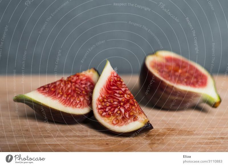 Aufgeschnittene Feige auf Holz aufgeschnitten lecker saftig Fruchtfleisch gesund Obst Ernährung rot