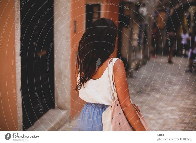 800 I Eine Frau die im Sommer Urlaub eine Gasse entlanggeht, Rückansicht braungebrannt sommerlich wehendes Haar Süden mediteran Altstadt abwenden brünett