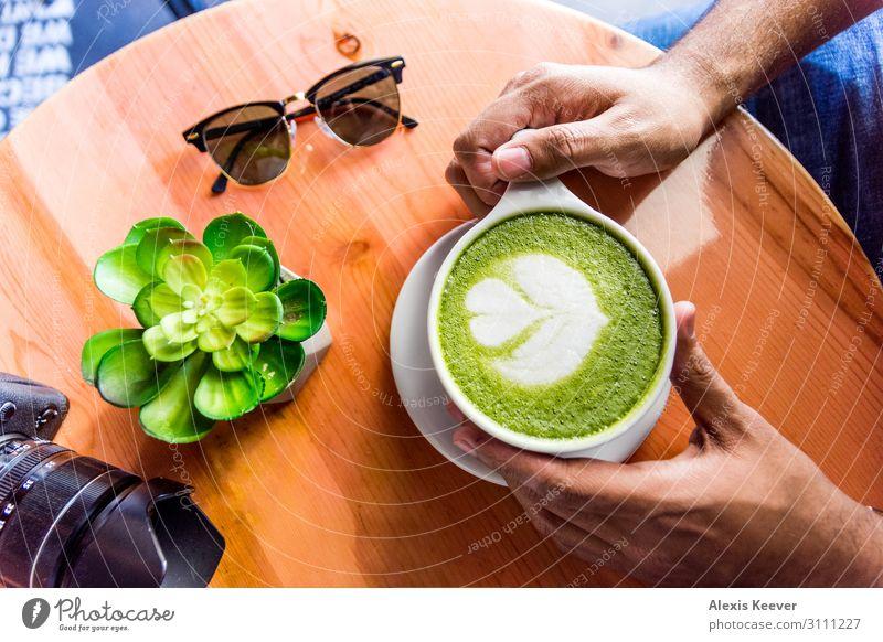 Mann mit Matcha Grüner Tee Latte Kunst auf einem Tisch in einem Café. Lebensmittel Kaffeetrinken Getränk Heißgetränk Latte Macchiato Espresso Tasse Lifestyle