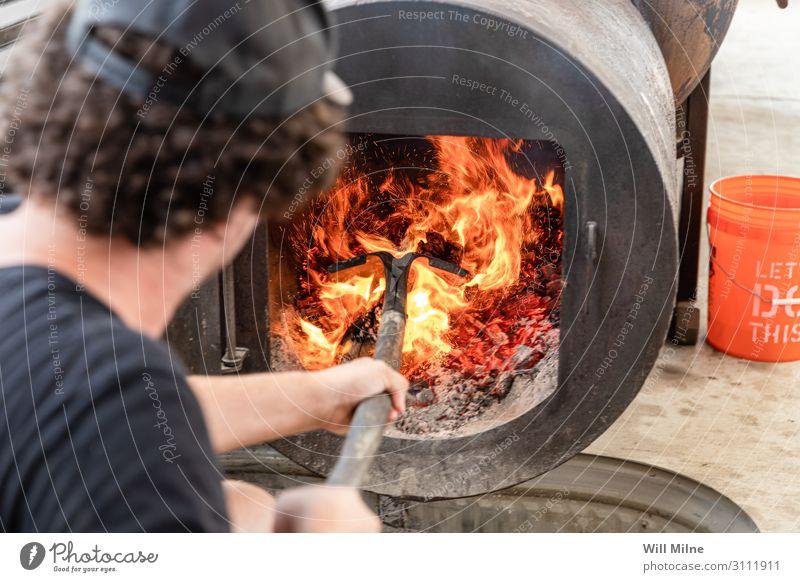 Mann schürt Feuer in einem Raucher Grill Grillen Grillplatz Fleisch Holz Flamme heiß heizen Schaufel schaufeln Essen zubereiten kochen & garen Koch Rauchen