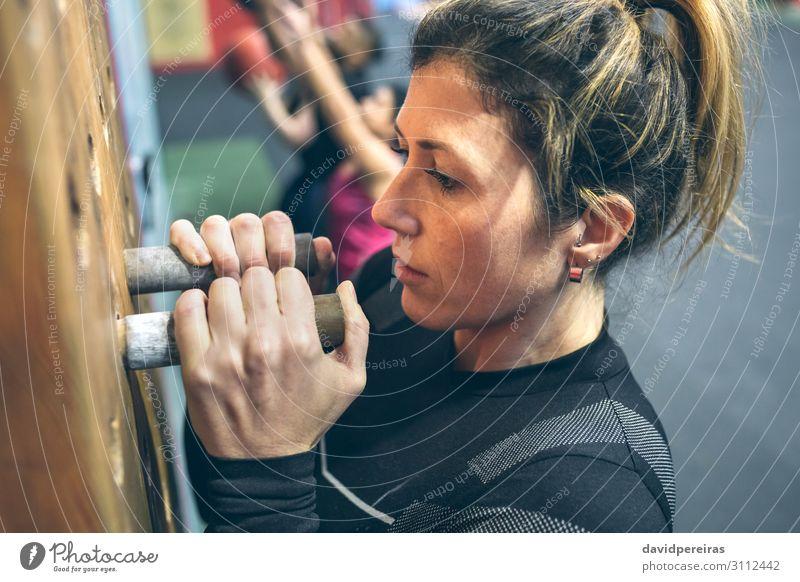 Frau, die an der Stecktafel hängt. Lifestyle Körper Sport Mensch Erwachsene Hand Fitness sportlich authentisch stark Kraft Steckplatte aufhängen durchkreuzen