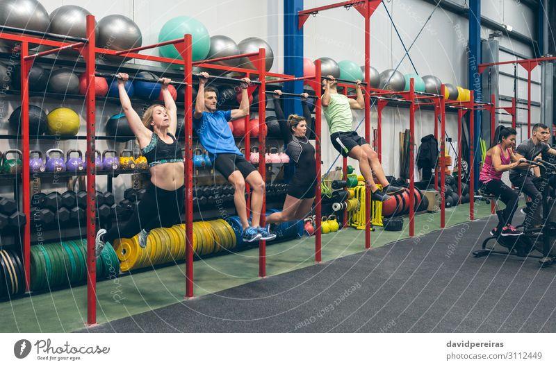 Athleten, die Pull-Ups machen und Airbike in der Turnhalle. Sport Ball Mensch Frau Erwachsene Mann Menschengruppe Fitness authentisch Klimmzüge kippen