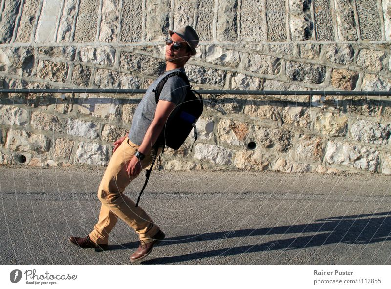 Ein Mann mit Sonnenbrille, Hut und Rucksack läuft eine Straße hinab in einem weit nach hinten gelehnten Gang maskulin Junger Mann Jugendliche Erwachsene 1