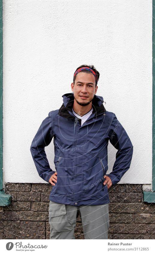 Mann mit Bandana und Regenjacke und offenem Gesichtsausdruck vor weißer Wand wandern maskulin Junger Mann Jugendliche Erwachsene 1 Mensch 30-45 Jahre Mauer Hose