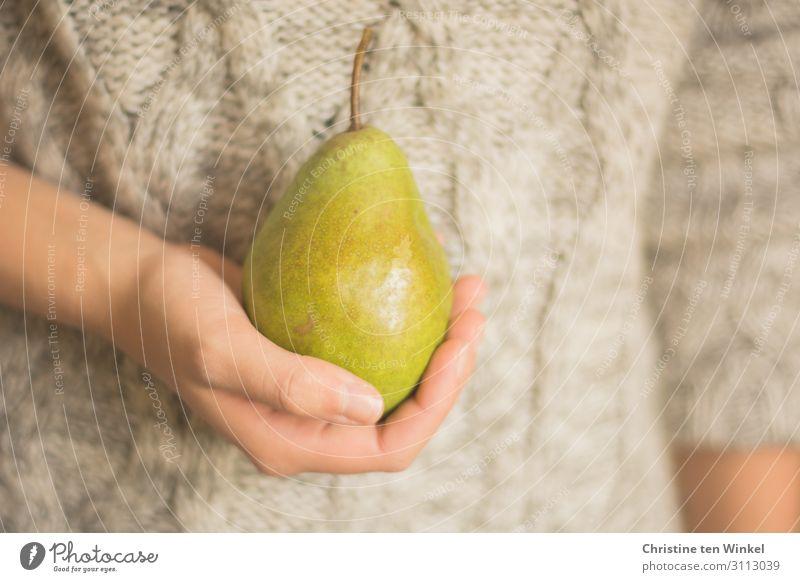 junge Frau im Zopfpullover hält Birne vor sich in der Hand Lebensmittel Frucht Birnenstiel Ernährung Bioprodukte Vegetarische Ernährung Mensch feminin