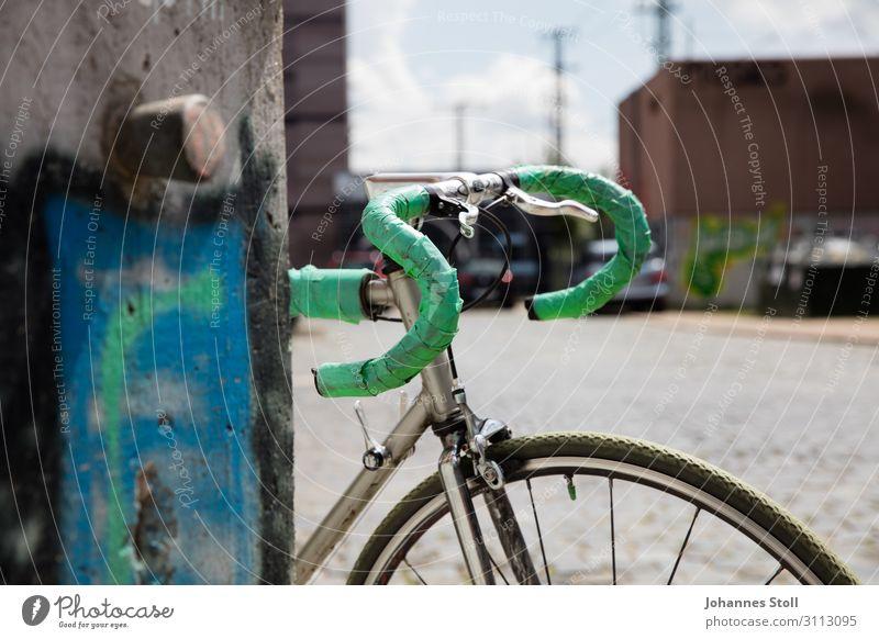 Vintage-Rennrad, das sich an die Wand lehnt, in städtischer Umgebung. Lifestyle Design Fahrradtour Fahrradfahren Himmel Sommer Stadt Fabrik Mauer Stein Metall