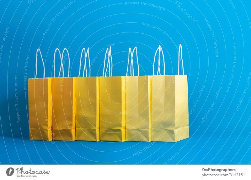 Gelbe Einkaufstaschen auf blauem Hintergrund, Einkaufskonzept Lifestyle kaufen Freude Glück Winter Feste & Feiern Weihnachten & Advent Silvester u. Neujahr