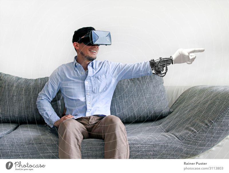 Mann auf dem Sofa mit Virtual-Reality-Brille und virtuellem Arm Wirtschaft Medienbranche Telekommunikation sprechen Headset Computer Hardware VR-Brille maskulin
