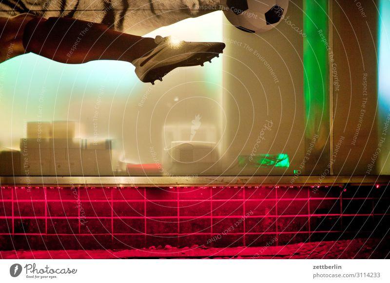 Dynamik im Schaufenster Fassade Fenster Stadtzentrum Menschenleer Textfreiraum Werbung Werbebranche Fuß Beine Wade Fußball Fußballschuhe stollen Schuss pass