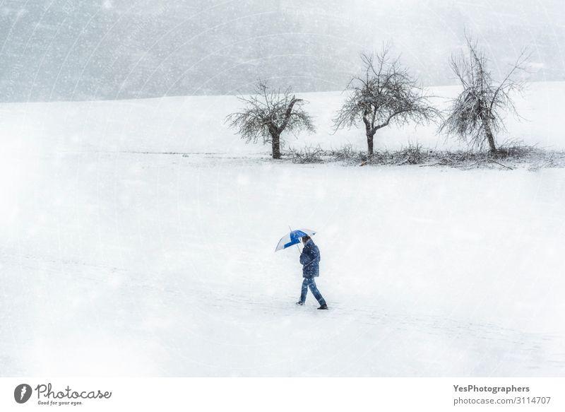 Schneesturmlandschaft. Mann geht durch den Schneefall. Winterwetter wandern Erwachsene Natur Klimawandel schlechtes Wetter Unwetter Sturm weiß Einsamkeit