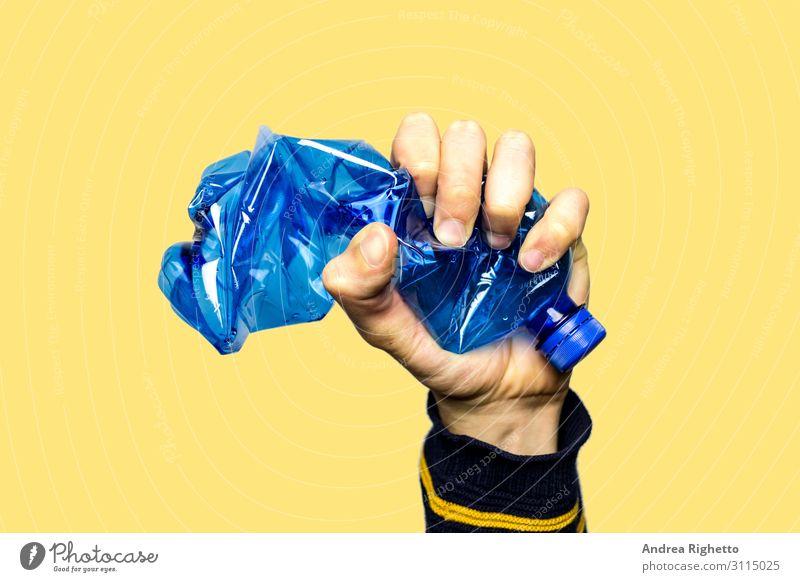 Konzept zur Beendigung der Kunststoffverschmutzung, der globalen Erwärmung, des Recyclings von Kunststoffen, frei von Kunststoffen. Eine leere blaue Plastikflasche wird als Zeichen des Protests mit der Hand fest zusammengedrückt. Gelber Hintergrund mit einem isolierten Thema