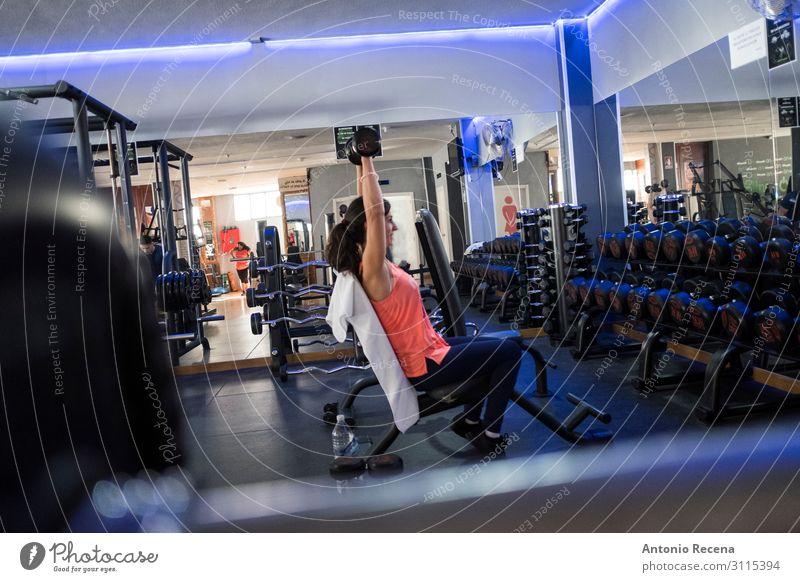 Frau beim Training im Fitnessstudio mit Gewichten Lifestyle Sport Sportler Erwachsene Lächeln muskulös Einsamkeit anstrengen Erwachsene mittleren Alters