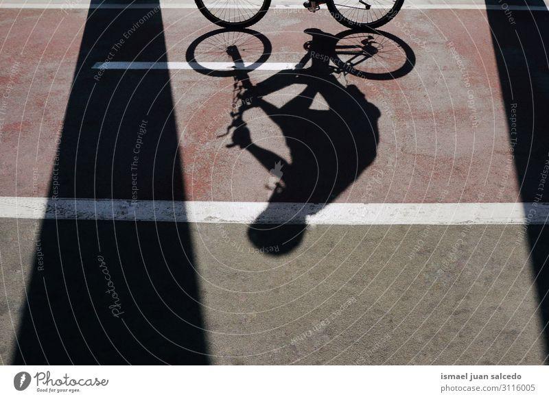 Mann auf dem Fahrrad Schatten Silhouette auf der Straße Fahrradfahren Sonnenlicht Boden Asphalt Hintergrund neutral abstrakt Verkehr Zyklus Sitz Wagenräder