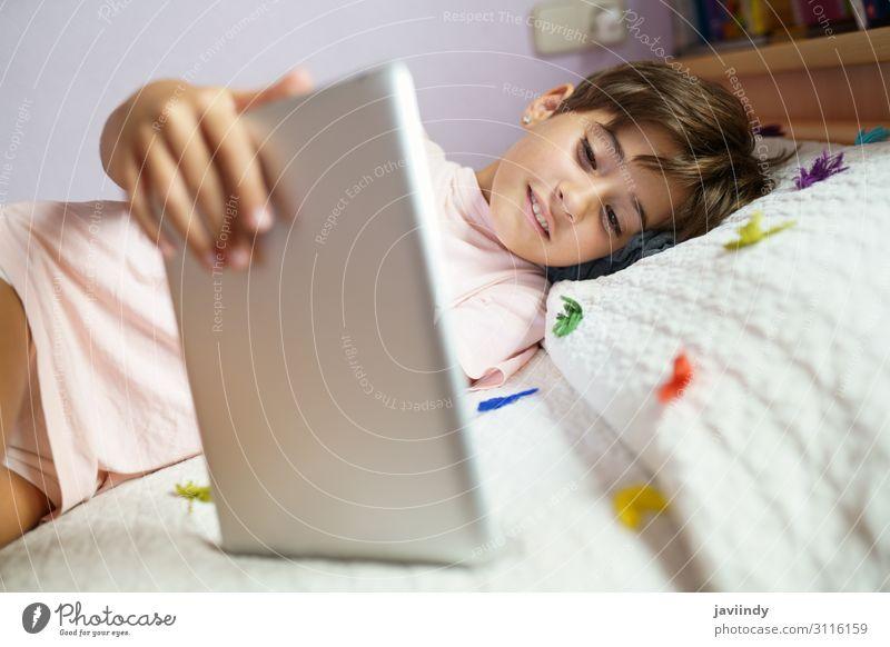 Süßes Mädchen, das einen Tablet-Computer in ihrem Schlafzimmer benutzt. Lifestyle Freude Glück schön Gesicht Freizeit & Hobby Spielen Kind Schule