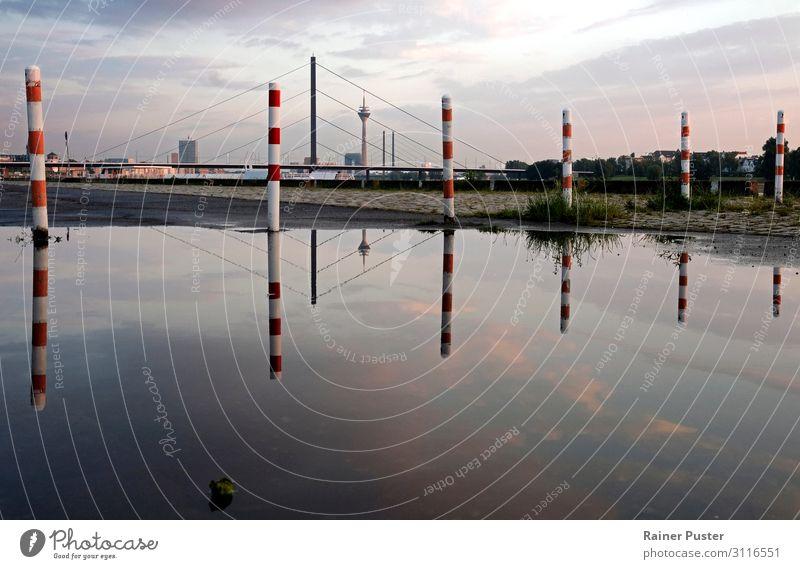 Die Skyline von Düsseldorf spiegelt sich nach dem Regen in einer großen Pfütze Himmel Wolken Sonnenaufgang Sonnenuntergang Stadtzentrum Brücke Turm Wahrzeichen