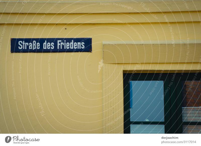Straße des Friedens heißt das Straßenschild an der Mauer. Ein Teil von einem Fenster ist noch zu sehen. Design Freude Ausflug Umwelt Sommer Schönes Wetter