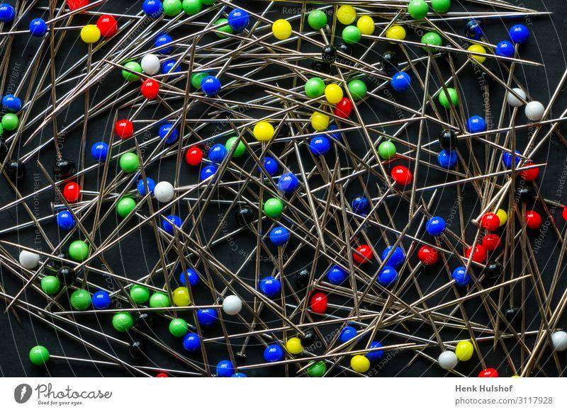 Ein Haufen mehrfarbiger Rundkopfstifte auf schwarzem Hintergrund. Metall Kunststoff blau gelb grün rot weiß Kopfstift Nähnadel stechend Stahl Farbfoto