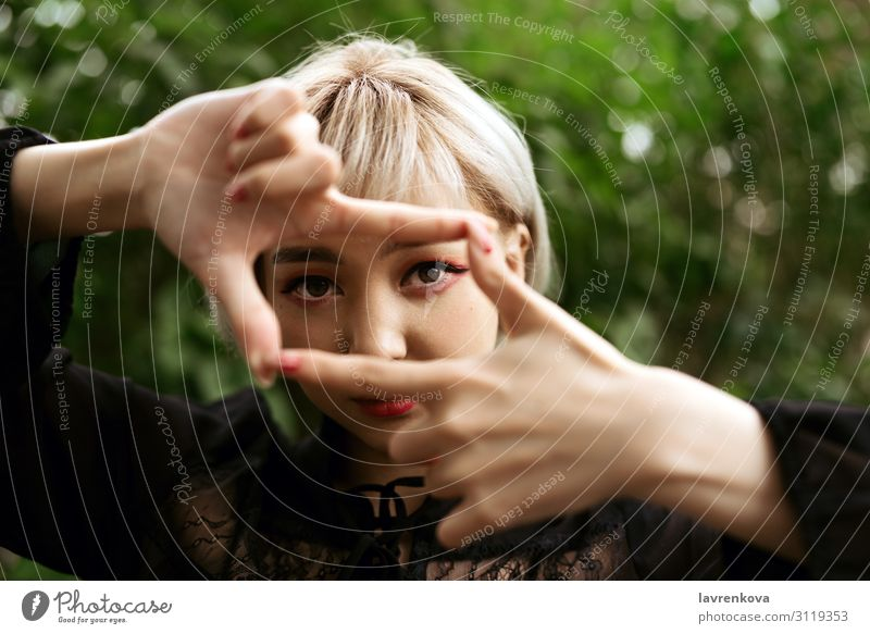Nahaufnahme einer blonden Frau, die eine Rahmengeste macht. Auge Park Photo-Shooting Hand Lifestyle Gesicht Asiate 18-30 Jahre Junge Frau Mensch schön
