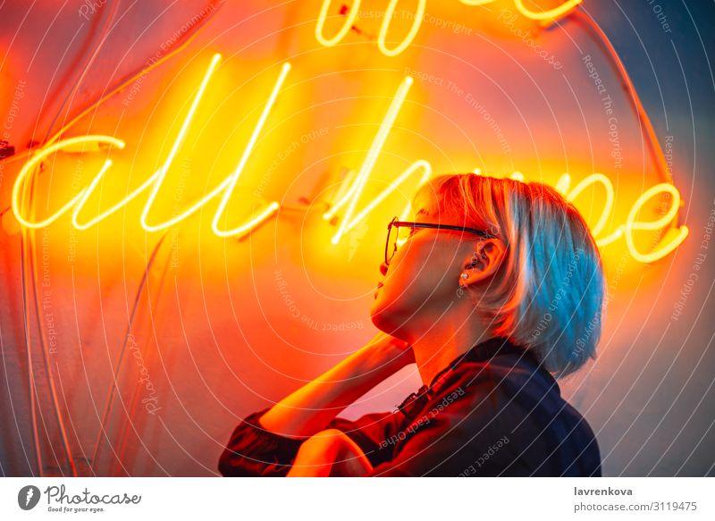 Brillenträgerinnen vor dem Neonlichtschild Asiate blond Frau Junge Frau Mädchen Beleuchtung Licht Nachtleben orange Porträt rot kurzhaarig Kurzhaarschnitt