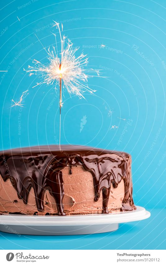 Schokoladenglasierter Geburtstagskuchen mit einer Wunderkerze. Neujahrstorte Dessert Feste & Feiern lecker Weihnachtskuchen Hintergrund Geburtstagstorte