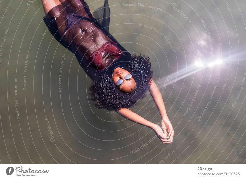 Schöne junge afroamerikanische Frau, die in einem Pool schwimmt. Lifestyle Freude schön Erholung Schwimmbad Freizeit & Hobby Spielen Ferien & Urlaub & Reisen