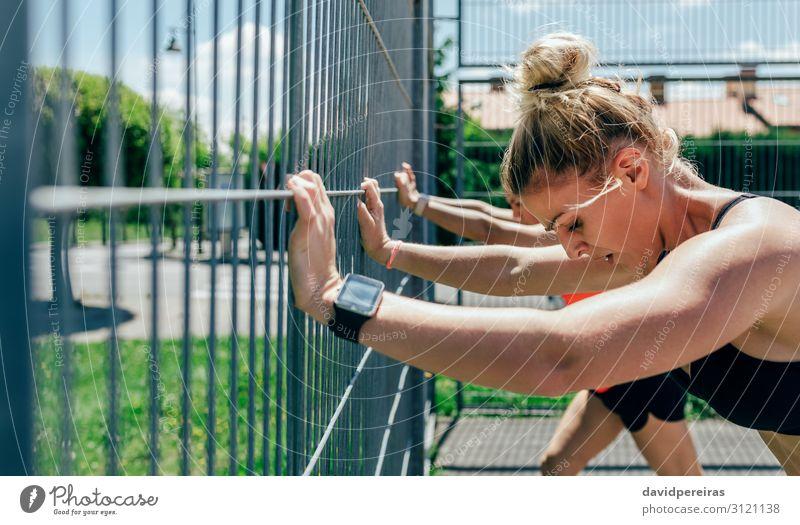 Zwei Sportlerinnen auf einem Zaun gestützt Brötchen Lifestyle schön Körperpflege Mensch Frau Erwachsene Freundschaft brünett blond Fitness sportlich stark Kraft