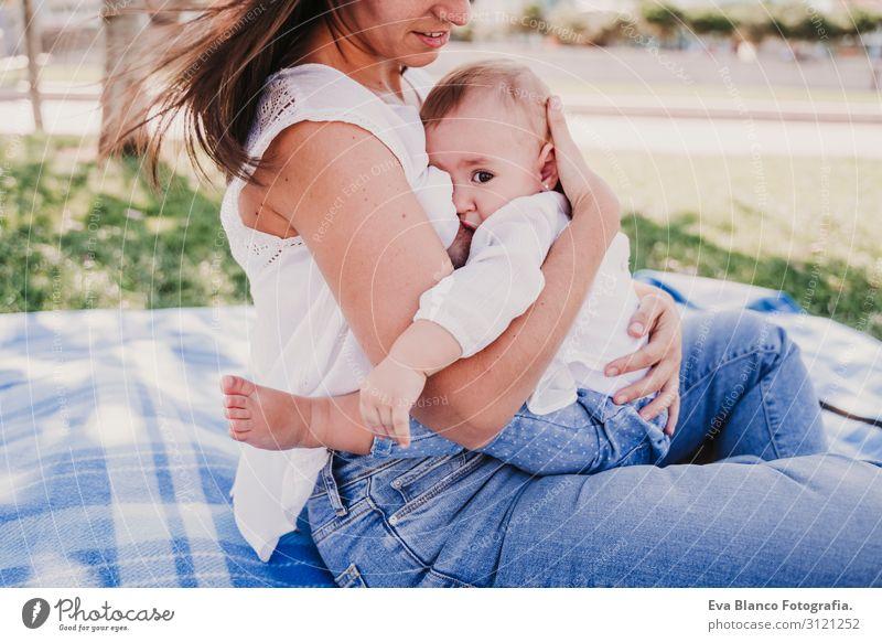 junge Mutter stillen, die ihr kleines Mädchen im Freien in einem Park füttert. Essen Lifestyle Freude Glück schön Spielen Sommer Sonne Kindererziehung feminin