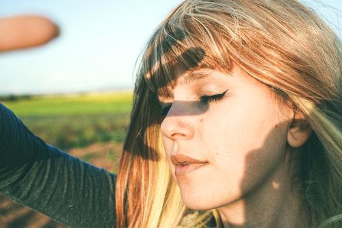 Junge Frau bedeckt die Sonne mit ihrer Hand. Lifestyle schön Gesicht Leben Sommer Mensch feminin Jugendliche Erwachsene 1 18-30 Jahre Herbst Mode blond