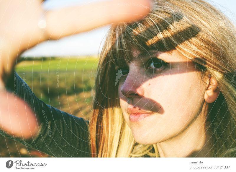 Junge Frau bedeckt die Sonne mit ihrer Hand. Lifestyle schön Haare & Frisuren Gesicht Leben Wohlgefühl Sinnesorgane Sommer Mensch feminin Jugendliche Erwachsene