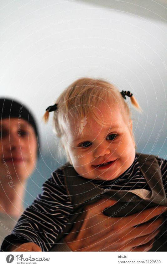 Papa läßt seine lachende, glückliche, fröhliche Tochter mit kleinen Zöpfen, fliegen. Kind hoch gehoben, in der Hand des Vaters, zuhause in der Wohnung. Mensch