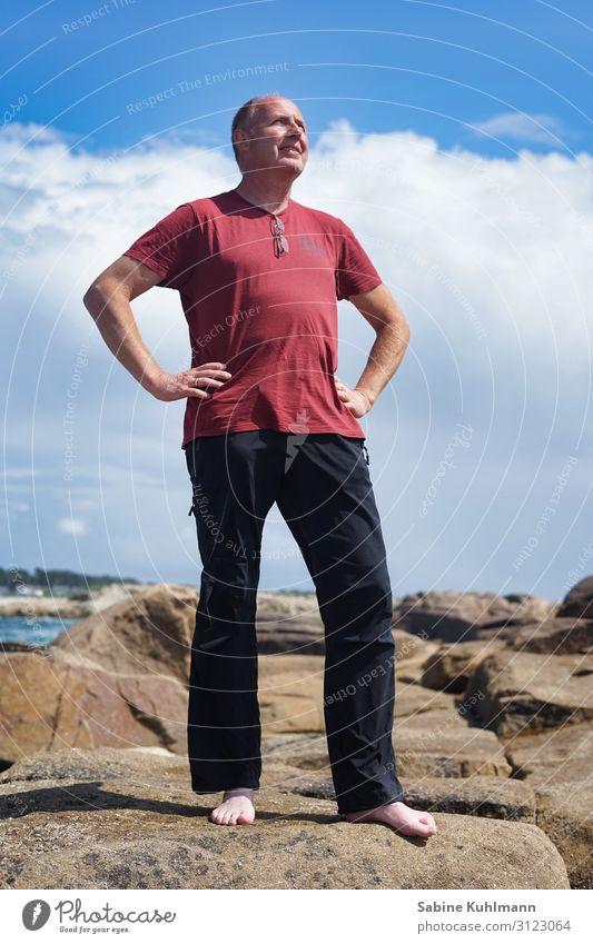 Urlaub Mensch maskulin Mann Erwachsene 1 45-60 Jahre Natur Himmel Sommer Schönes Wetter Küste Bekleidung T-Shirt Hose Stein beobachten Blick stehen einfach