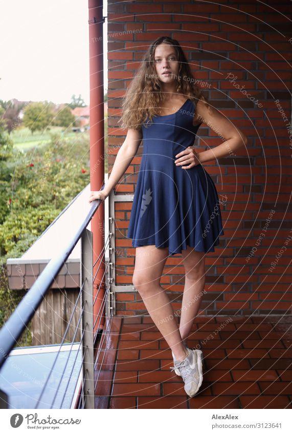 Portrait einer jungen, großen Frau auf einem Balkon mit Ziegelsteinmauer und Aussicht auf den Garten Lifestyle Stil schön Leben Wohnung Haus Backstein