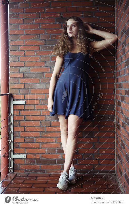 Portrait einer jungen, großen Frau auf einem Balkon mit Ziegelsteinmauer Lifestyle Stil schön Leben Wohnung Haus Backstein Junge Frau Jugendliche 18-30 Jahre