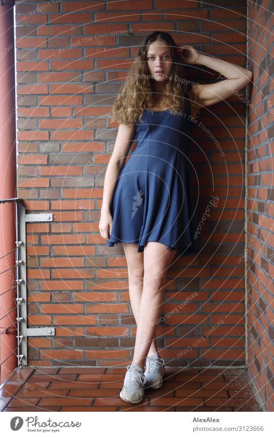 Portrait einer jungen, großen Frau auf einem Balkon mit Ziegelsteinmauer Lifestyle Stil schön Leben Wohnung Backstein Junge Frau Jugendliche 18-30 Jahre